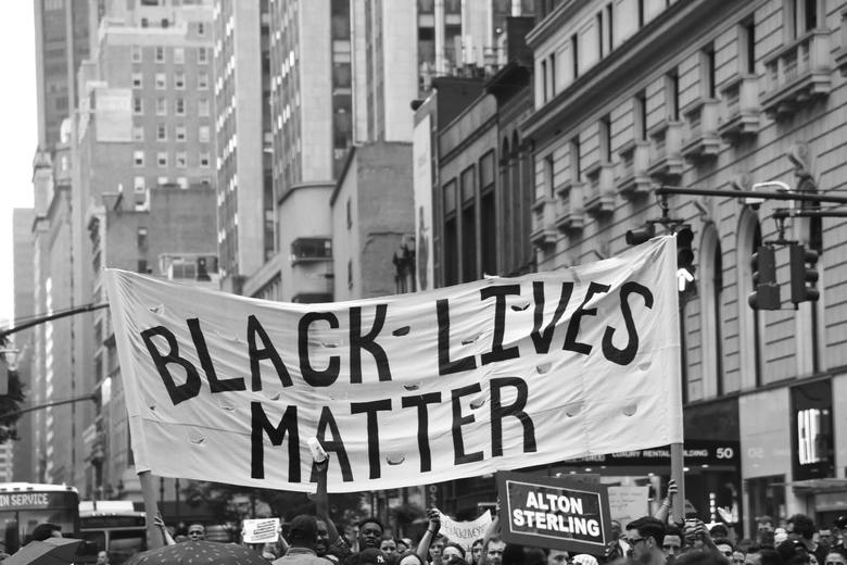 Black and white image of a group of people in a city, peacefully marching holding a sign 'Black Lives Matter'
