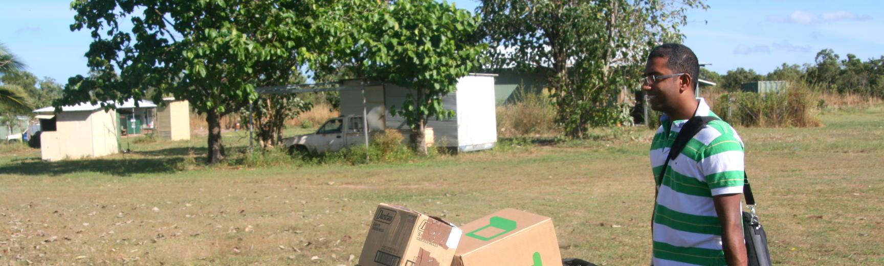 Rangan Srikhanta holding wheelbarrow full of boxes