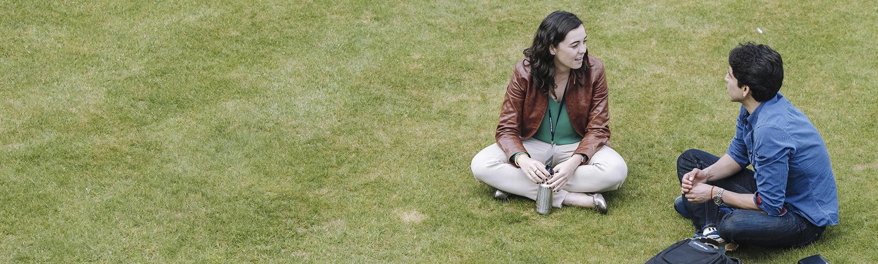 Macarena Hernandez de Obseo and Alexander Wankel having a conversation sat on the grass