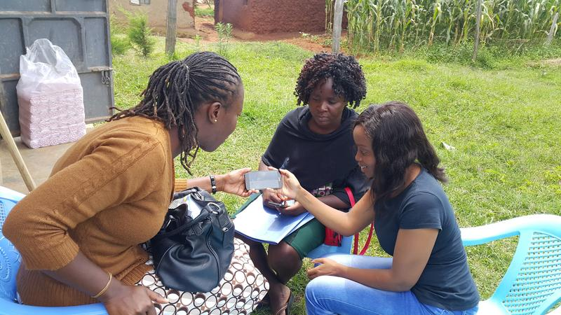 Dr Diana training two field workers on utilising the mobile application