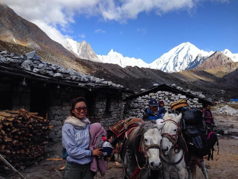 Tsechu Dolma hiking to one of the MRP's sites with two horses