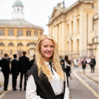 dawn musil standing in traditional Oxford uniform outside the sheldonian theatre